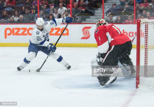 Tampa Bay Lightning Winger Gabriel Dumont prepares to shoot the puck at goal against Ottawa Senators Goalie Mike Condon during the NHL game between...