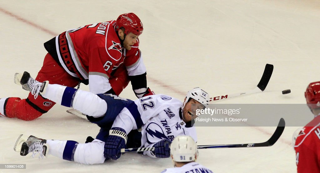 Tampa Bay Lightning's Ryan Malone (12) and Carolina Hurricanes' Tim Gleason (6) go for the puck during second-period action at PNC Arena in Raleigh, North Carolina, Tuesday, January 22, 2013. The Lightning defeated the Hurricanes, 4-1.