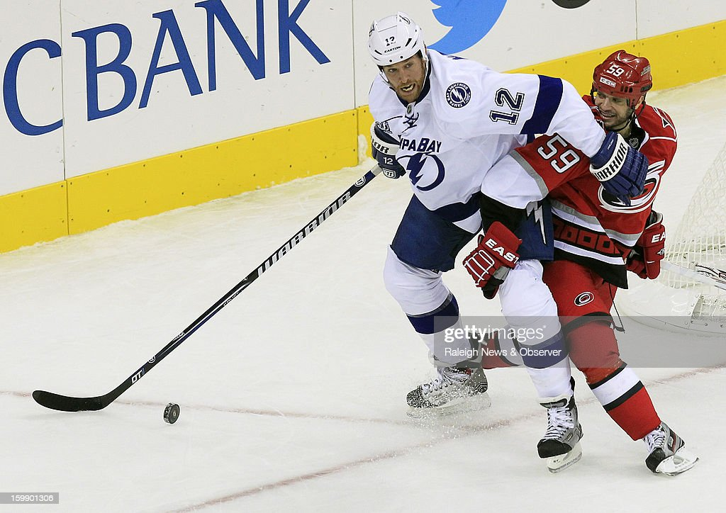 Tampa Bay Lightning's Ryan Malone (12) battles Carolina Hurricanes' Chad LaRose (59) for the puck during third-period action at PNC Arena in Raleigh, North Carolina, Tuesday, January 22, 2013. The Lightning defeated the Hurricanes, 4-1.