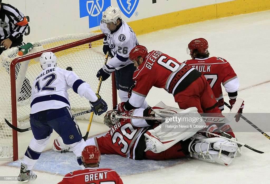 Tampa Bay Lightning's Ryan Malone (12) scores a goal past Carolina Hurricanes' Cam Ward (30), Tim Gleason (6), Justin Faulk (27) and Tampa Bay Lightning's Martin St. Louis (26) during third-period action at PNC Arena in Raleigh, North Carolina, Tuesday, January 22, 2013. The Lightning defeated the Hurricanes, 4-1.