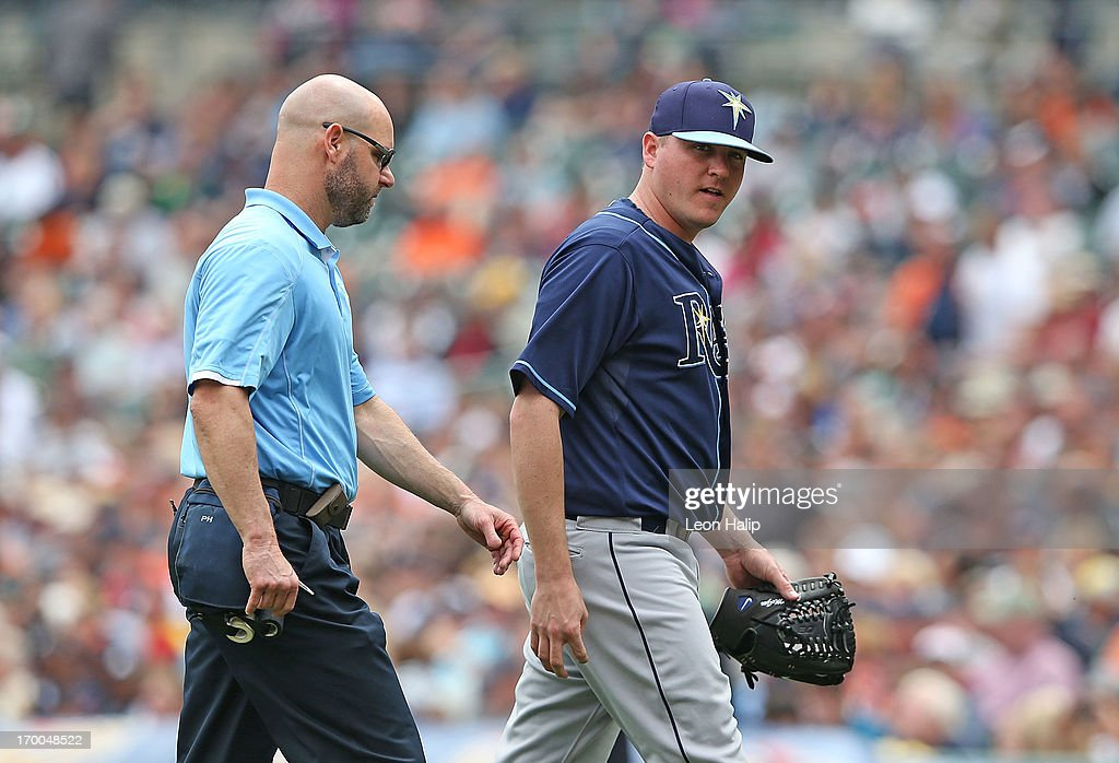 Tampa Bay Rays head athlletic trainer Ron Porterfield walks back to the dugout with pitcher <a gi-track='captionPersonalityLinkClicked' href=/galleries/search?phrase=Jake+McGee+-+Baseball+Player&family=editorial&specificpeople=15096866 ng-click='$event.stopPropagation()'>Jake McGee</a> #57 after he was hit in the leg by a ball hit by <a gi-track='captionPersonalityLinkClicked' href=/galleries/search?phrase=Miguel+Cabrera&family=editorial&specificpeople=202141 ng-click='$event.stopPropagation()'>Miguel Cabrera</a> #24 of the Detroit Tigers in the seventh inning of the game at Comerica Park on June 6, 2013 in Detroit, Michigan. The Tigers defeated the Ray 5-2.