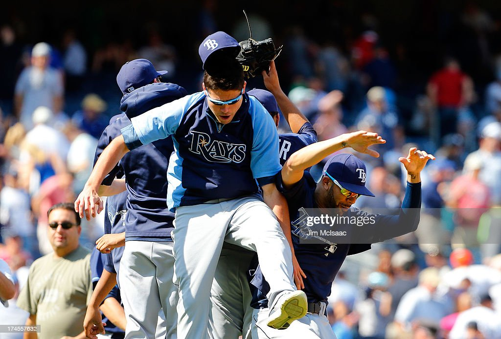 Tampa Bay Rays pitchers Matt Moore #55 (C) and David Price #14 celebrate after teammate Chris Archer #22 of the Tampa Bay Rays pitch a complete game shut out against the New York Yankees at Yankee Stadium on July 27, 2013 in the Bronx borough of New York City.