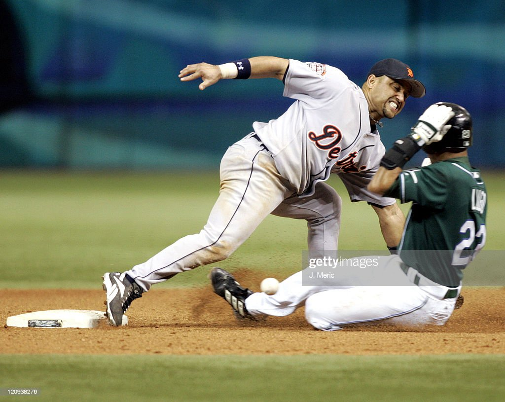 Tampa Bay's Julio Lugo slides in safely with a steal as Detroit's Placido Polanco tries to get the throw in Thursday night's game at Tropicana Field...