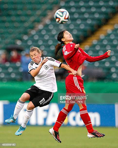 Tan Ruyin of China PR wins a header against Linda Dallmann of Germany at Commonwealth Stadium on August 8 2014 in Edmonton Canada
