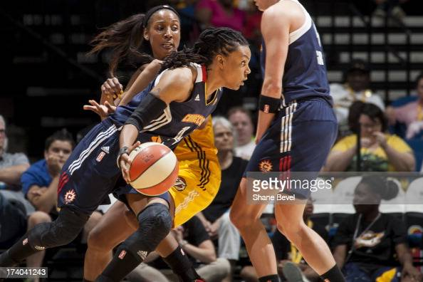 Tan White of the Connecticut Sun drives past Candice Wiggins of the Tulsa Shock during the WNBA game on July 19 2013 at the BOK Center in Tulsa...