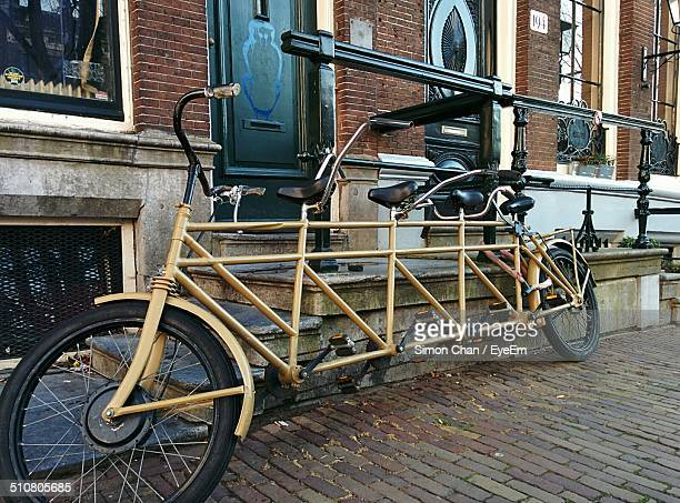 Tandem bicycle parked outside house