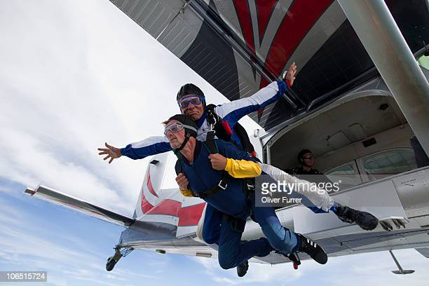 Tandem skydive couple jumping out of the plane.