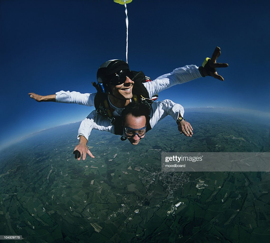 Tandem skydivers over earth