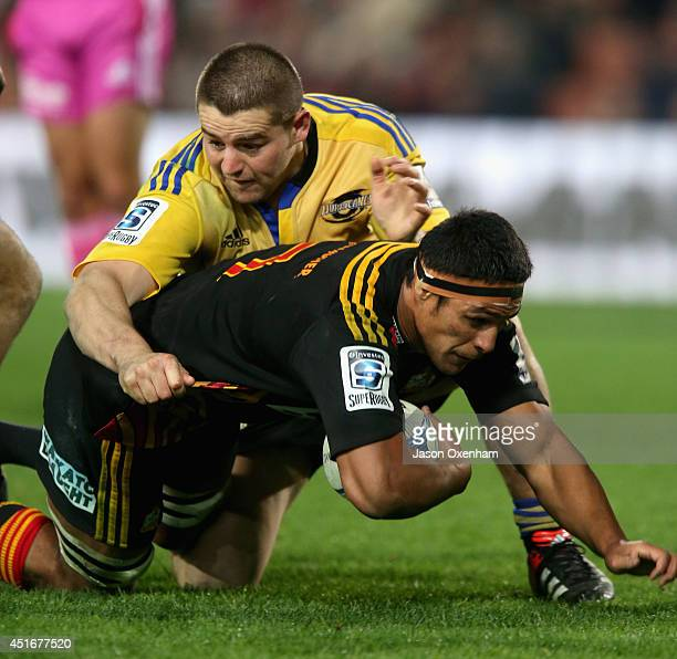 Tanerau Latimer of the Chiefs is brought down by Dane Coles of the Hurricanes during the round 18 Super Rugby match between the Chiefs and the...