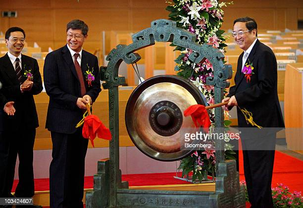 Tang Shuangning chairman of China Everbright Group Ltd left and Xu Zhengsheng party secretary of Shanghai municipality ring a gong to mark the bank's...