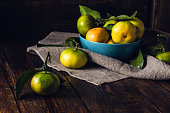 Still Life with Tangerines in Blue Bowl. Selective Focus on Single Tangerine.
