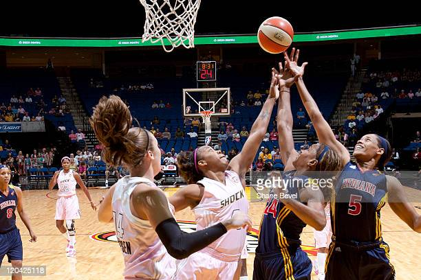 Tanglea Smith and Tamika Catchings of the Indiana Fever battle with Amber Holt of the Tulsa Shock for a rebound during the WNBA game on August 5 2011...