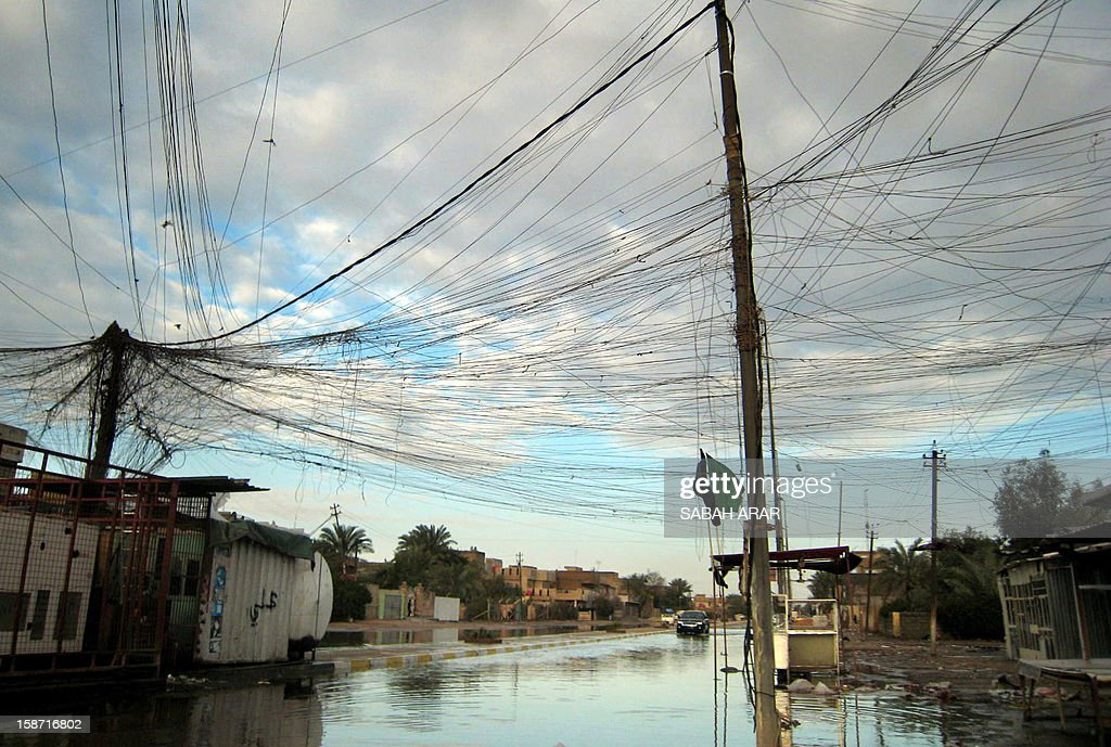 Tangled electrical wires are seen over a rain flooded street in the capital Baghdad on December 26, 2012.