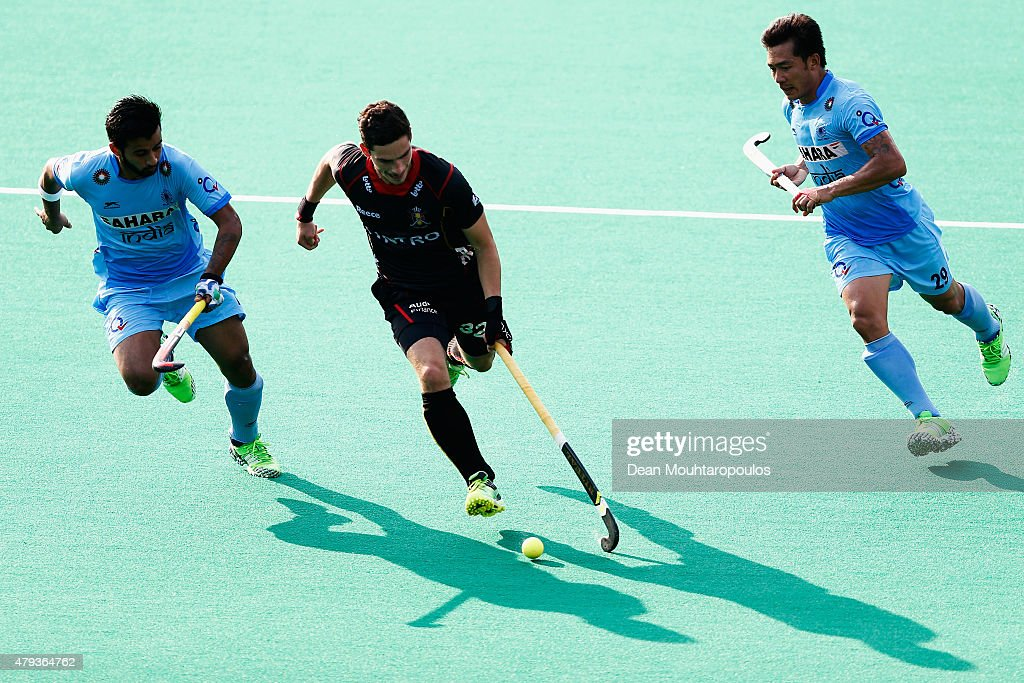 Tanguy Cosyns #32 of Belgium is chased by Chinglensana Kangujam and <a gi-track='captionPersonalityLinkClicked' href=/galleries/search?phrase=Manpreet+Singh+-+Field+Hockey+Player&family=editorial&specificpeople=16029378 ng-click='$event.stopPropagation()'>Manpreet Singh</a> of India during the Fintro Hockey World League Semi-Final match between India and Belgium held at KHC Dragons Gemeentepark Stadium on July 3, 2015 in Brasschaat, Belgium.