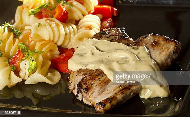 A tangy Dijon mustard sauce flavors juicy tender pork for this Frenchstyle dinner Red peppers and tomatoes tossed with pasta complete this quick meal