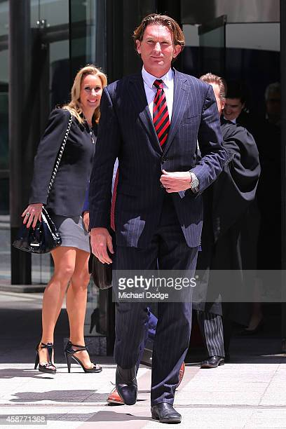 Tania Hird watches husband and Essendon Bombers coach James Hird walk out to speak to media before leaving Melbourne Federal Court on November 11...