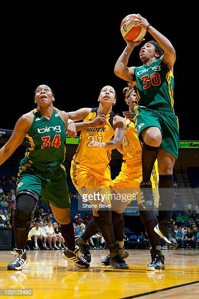 Tanisha Wright drives to the hoop as her teammate Le'coe Willingham of the Seattle Storm holds back Jennifer Lacy and Amber Holt of the Tulsa Shock...