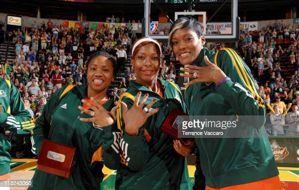 Tanisha Wright Le'coe Willingham and Ashley Robinson of the Seattle Storm show off their 2010 WNBA Championship Rings before the game against the...
