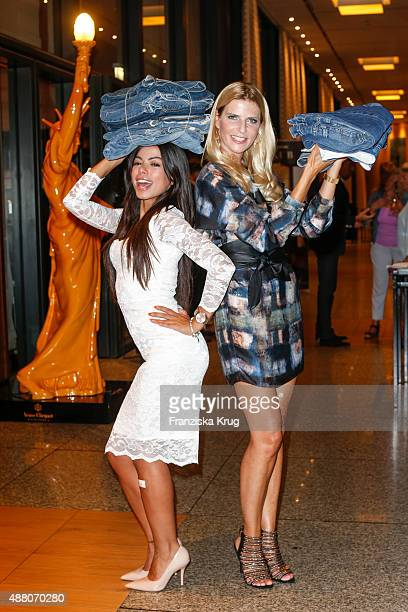 Tanja Buelter and Fernanda Brandao pose with jeans which will be handed over to refugees during the Promi Shopping Queen with Tanja Buelter and...