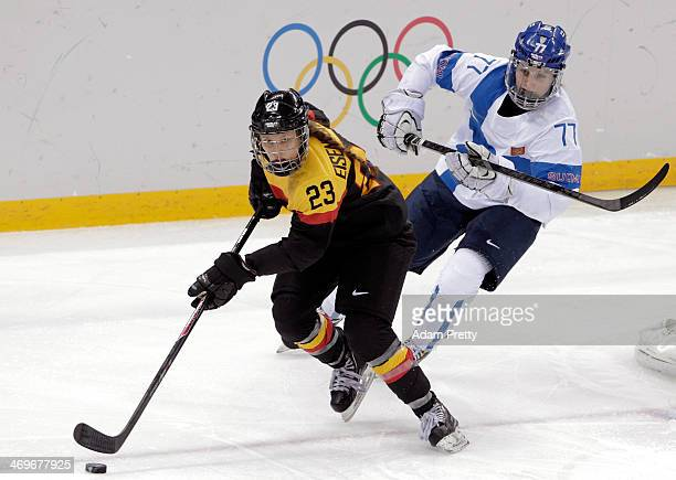 Tanja Eisenschmid of Germany handles the puck against Susanna Tapani of Finland during the Women's Ice Hockey Classification game on day nine of the...