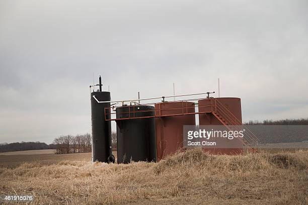 A tank battery used for temporary storage of crude oil pumped from nearby wells sits in a farmer's field on January 20 2015 near McLeansboro Illinois...