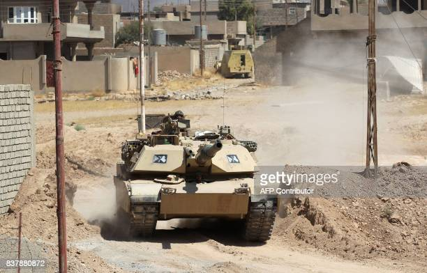 A tank belonging to the Iraqi forces backed by Shiite fighters from the Popular Mobilization Forces advances inside alNour neighbourhood in eastern...