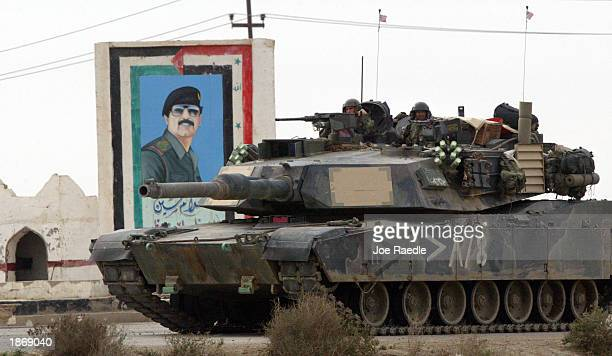 A tank from the United States Marine Task Force Tarawa sets up position in front of a painting of Saddam Hussein March 24 2003 at the garrison of the...