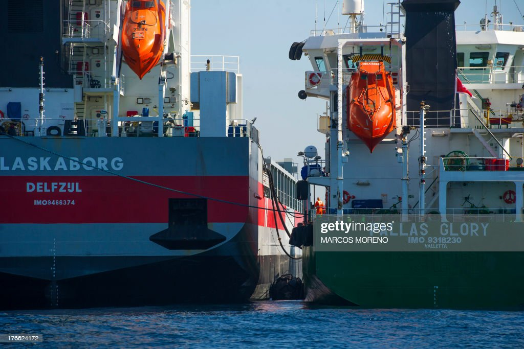 A tanker delivers fuel by pipe to a ship in the bay of Algeciras, near Gibraltar, on August 16, 2013. Madrid is threatening to take action against Gibraltar's offshore refueling of ships, adding a new front in its row with London over contested waters around the British outpost on Spain's southern tip. Due to a lack of space on land to store fuel tanks, Gibraltar has tankers permanently anchored in its bay that store fuel which is then delivered by pipe to ships that dock beside them.