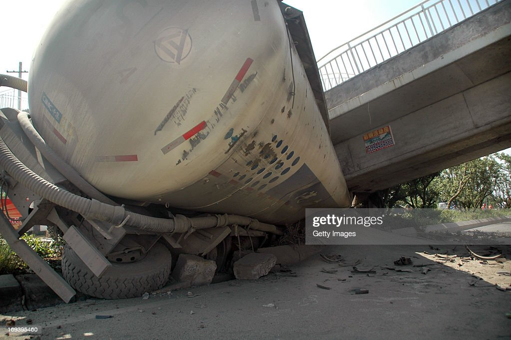 A tanker is crushed under a collapsed bridge on the west second ring road on May 23, 2013 in Guiyang, China. The bridge collapsed after a tanker crashed into one of its support. Another passing truck was struck, injuring two.
