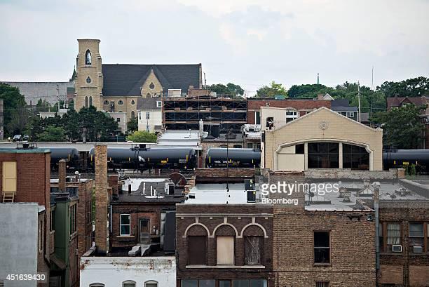 Tanker rail cars bearing UN 1267 petroleum crude oil class 3 hazardous materials placards travel on an elevated railway through Aurora Illinois US on...