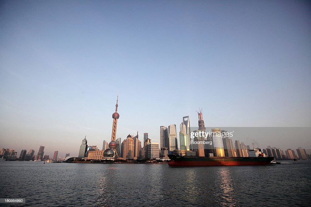 A tanker sails past commercial buildings in the Pudong area, seen from the Bund, in Shanghai, China, on Monday, Jan. 28, 2013. China's economic growth accelerated for the first time in two years as government efforts to revive demand drove a rebound in industrial output, retail sales and the housing market. Photographer: Tomohiro Ohsumi/Bloomberg via Getty Images