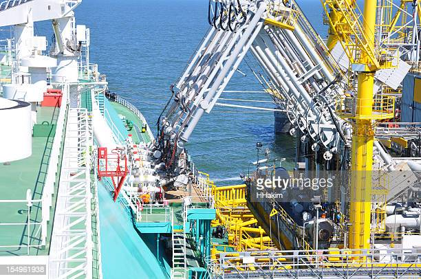 LNG tanker unloading cargo with a multi-handed crane