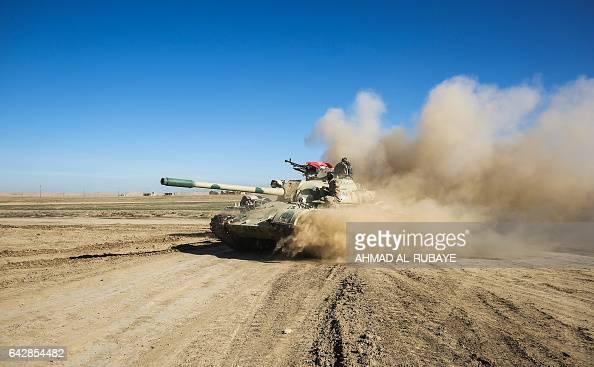 TOPSHOT Tanks and armoured vehicles of the Iraqi forces supported by the Hashed alShaabi paramilitaries advance towards the village of Sheikh Younis...