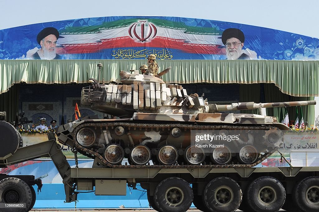 Tanks are transported past Major General Hassan Firoozabadi and other military commanders as they observe a parade commemorating the 31st anniversary...
