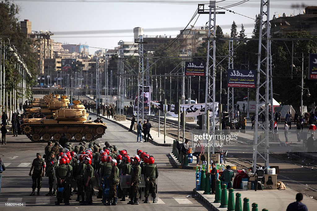 Tanks belonging to the Egyptian Republican Guard and members of the military police deploy outside the presidential palace in Cairo on December 11, 2012. Protesters started to gather in the Egyptian capital for rival rallies for and against a divisive constitutional referendum proposed by President Mohamed Morsi.