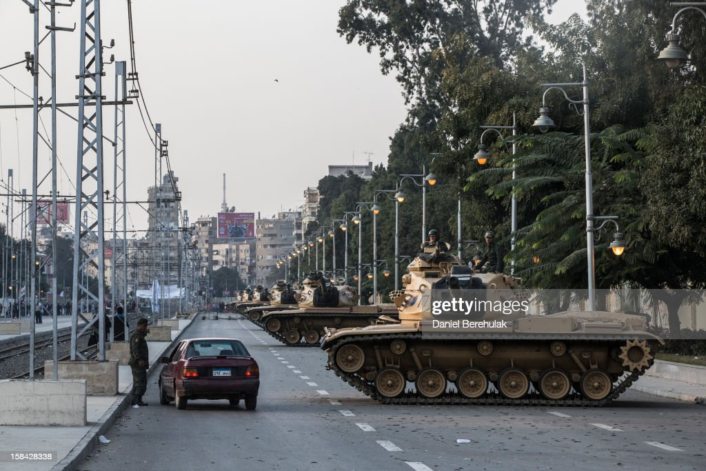 Tanks line up in front of the presidential palace on December 16, 2012 in Cairo, Egypt. Egyptians went to the polls yesterday to vote in a referendum on a proposed constitution that could change the character of Egypt and gradually bring its laws closer to Sharia, or Islamic law. The Freedom and Justice Party reported that unofficial results, based on 99.2 percent of polling stations, show 56.5 percent of voters approving the constitution and 43.5 percent rejecting it.
