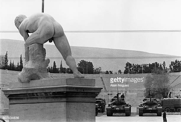 Tanks Occupying Athens Stadium Seen Past a Greek Statue of an Athlete