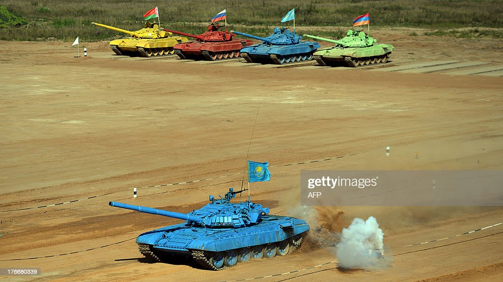Tanks of (back L-R) Belarus, Russian, Kazakh and Armenian teams line up as they compete during tank biathlon, a new paramilitary sport about armor races and precision gunnery near Alabino, outside Moscow, on August 17, 2013.