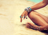 Woman is sitting in relaxed position on tropical sandy beach. Body parts. Tanned girl in lotus position dressed in silver jewelry,bracelets and rings.Boho style.