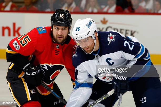 Tanner Glass of the Calgary Flames battle for position against Blake Wheeler of the Winnipeg Jets during an NHL game on October 7 2017 at the...
