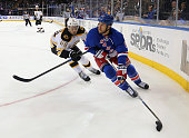 Tanner Glass of the New York Rangers carries the puck around Brian Ferlin of the Boston Bruins during the first period at Madison Square Garden on...