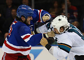 Tanner Glass of the New York Rangers fights with Andrew Desjardins of the San Jose Sharks during the third period at Madison Square Garden on October...