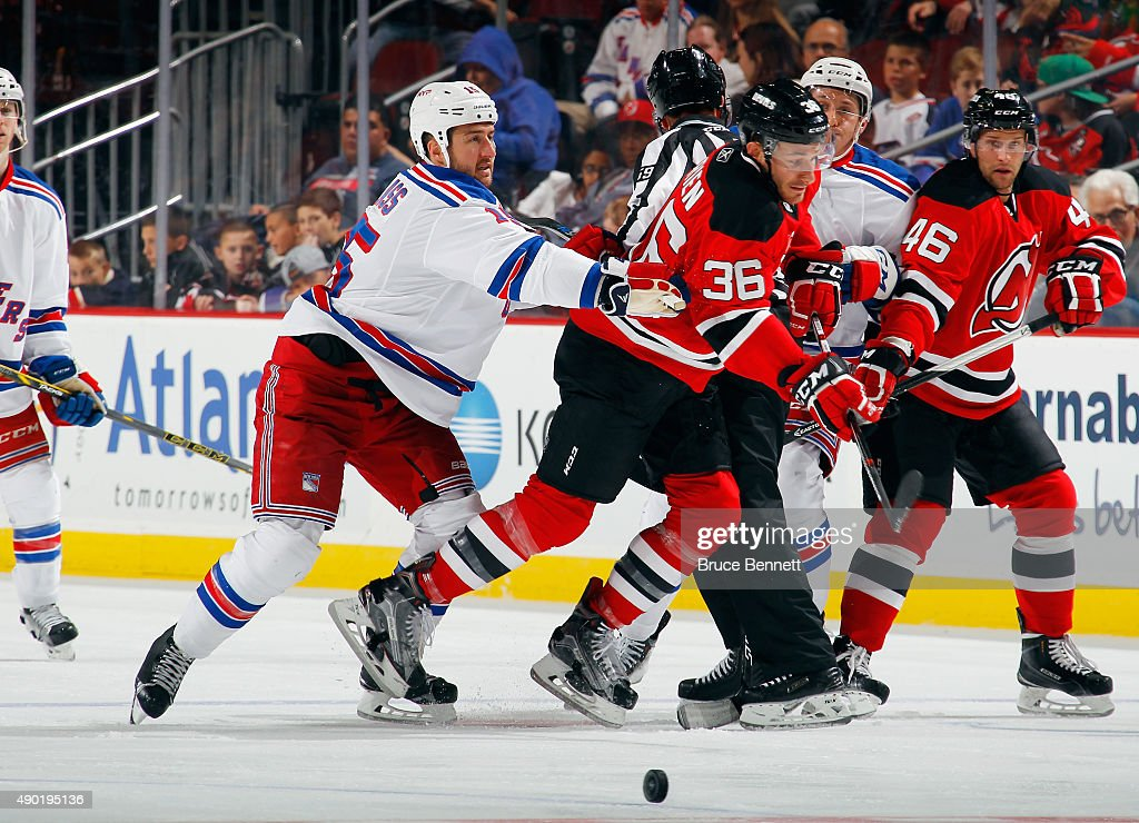 Tanner Glass of the New York Rangers hits Jim O'Brien of the New Jersey Devils during the third period during a preseason game at the Prudential...