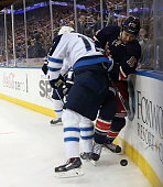 Tanner Glass of the New York Rangers is hit by Adam Lowry of the Winnipeg Jets at Madison Square Garden on November 1 2014 in New York City
