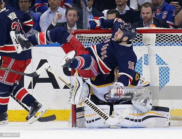 Tanner Glass of the New York Rangers is tripped up in front of Tuukka Rask of the Boston Bruins during the third period at Madison Square Garden on...