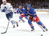 Tanner Glass of the New York Rangers skates with the puck against Cody Franson of the Toronto Maple Leafs at Madison Square Garden on October 12 2014...