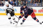 Tanner Glass of the Pittsburgh Penguins and Brandon Dubinsky of the Columbus Blue Jackets battle for the puck during the third period on March 28...