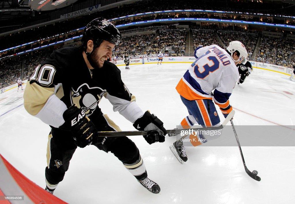 Tanner Glass #10 of the Pittsburgh Penguins attempts to lift the stick of Colin McDonald #13 of the New York Islanders during the game at Consol Energy Center on January 29, 2013 in Pittsburgh, Pennsylvania. The Islanders defeated the Penguins 4-1.