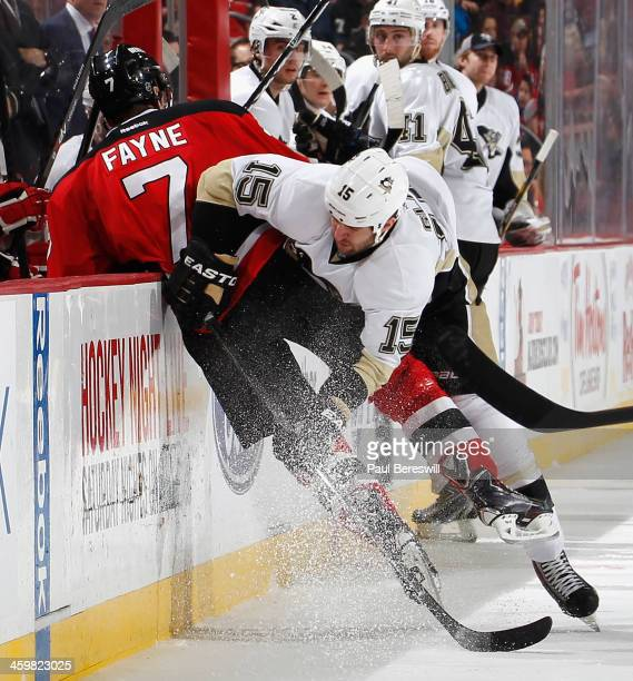 Tanner Glass of the Pittsburgh Penguins checks Mark Fayne of the New Jersey Devils into the boards during the second period of an NHL hockey game at...