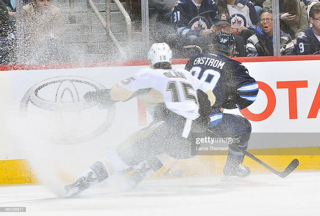 <a gi-track='captionPersonalityLinkClicked' href=/galleries/search?phrase=Tanner+Glass&family=editorial&specificpeople=4596666 ng-click='$event.stopPropagation()'>Tanner Glass</a> #15 of the Pittsburgh Penguins kicks up a spray of snow as he chases <a gi-track='captionPersonalityLinkClicked' href=/galleries/search?phrase=Tobias+Enstrom&family=editorial&specificpeople=2538468 ng-click='$event.stopPropagation()'>Tobias Enstrom</a> #39 of the Winnipeg Jets along the boards during third period action at the MTS Centre on April 3, 2014 in Winnipeg, Manitoba, Canada.